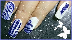 4 different nail art designs using white and blue nail polish
