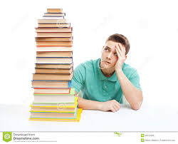 Picture Of Student Sitting At Desk Student Sitting At The Desk With High Books Stack Royalty Free