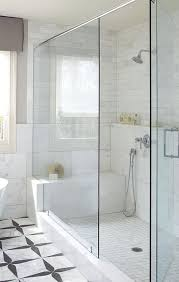 a walk in shower is filled with a mix of marble shower tiles lined