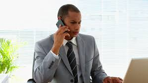 Cell Phone To Desk Phone A Busy Man On His Office Desk Phone Gets Paperwork Handed To Him
