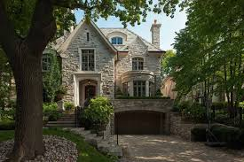 custom europan tudor style home design with white stacked stone