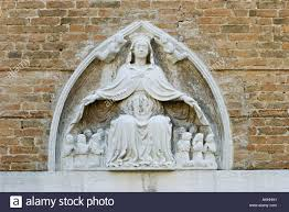carving of the virgin mary with angels and kneeling praying monks