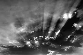 black and white sky with clouds and sun rays stock photo image