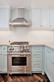 white cabinets on top blue on bottom blue cabinets light gray quartz counters mini mosaic