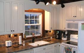 white kitchen cabinets with gray granite countertops after light