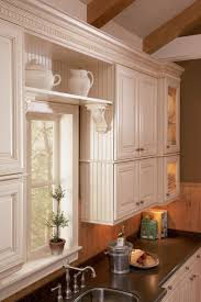 stone countertops white beadboard kitchen cabinets lighting