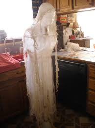 old spirit halloween props packing tape cheesecloth ghost to hang in trees done for under 10