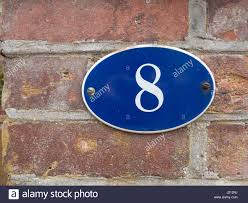 a house number plate outside blue with white number 8 oval on