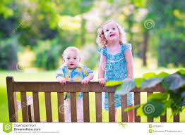 brother and sister standing on a park bench stock photo image