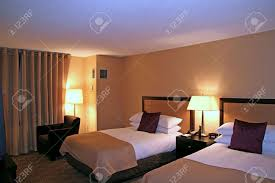 generic modern hotel room shot at night with lights on stock photo