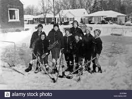 boys take a break from a hockey game on a neighbourhood back yard
