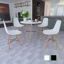 salle à manger blanche avec table ronde et chaises sans