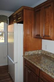 Deep Cabinet Above The Refrigerator And A Wood Panel On The Side