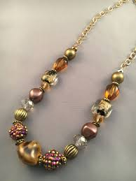 this necklace has a large gold chain with sparkly balls brown