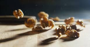 extreme macro italian organic walnuts falling on a wooden cutting