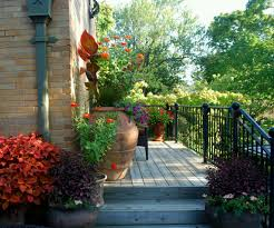 outdoor a terrace house with large pots with plants and flowers
