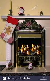 christmas stockings hang over a fireplace with a roaring fire in