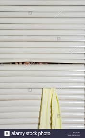 a person peeking through window blinds stock photo royalty free