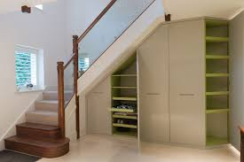 interior unusual white bookshelves under white wooden staircase