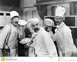 three chefs holding pies for a fight in the kitchen stock photo