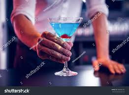 blue martini bartender serving blue martini bar stock photo 388580359