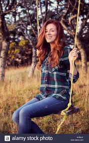 a carefree young women in jeans on a swing in a winter garden