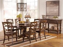 oval brown wooden expandable dining table with single legs