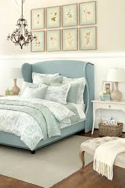 decorating with neutrals washed color palettes color patterns cottage bedroom from ballard designs i like the wing back style headboard in cool blue linen with nail head trim the eight botanical prints are lovely