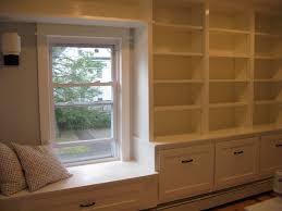 white wooden bookshelves beside white wooden window seat with