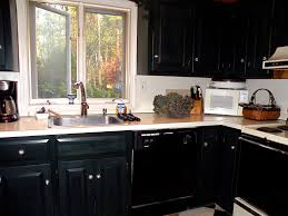 black wooden kitchen cabinet with white countertop and steel sink