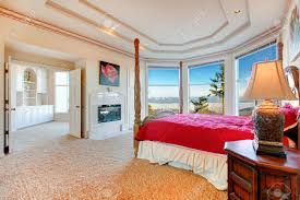 stunning luxury master bedroom with rich bedroom furniture and stunning luxury master bedroom with rich bedroom furniture and amazing angled glass wall overlooking picturesque view
