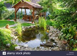 beautiful garden with bench and little pond to relax stock photo