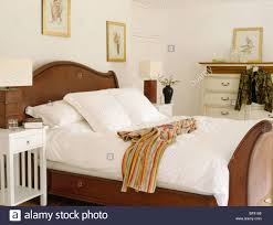 white cushions and bedlinen and striped bath robe on mahogany bed