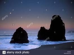 full moon setting at dawn over pacific ocean and coastal sea