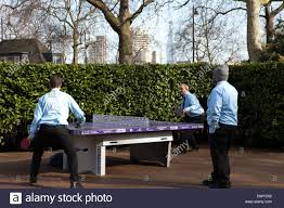 3 men in blue shirts playing table tennis in victoria embankment