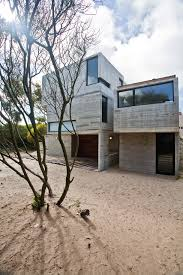 concrete house with industrial features on the beach by bak
