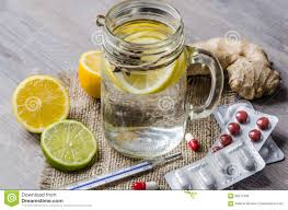 a maison jar with ginger and lemon tea with pills and thermometer