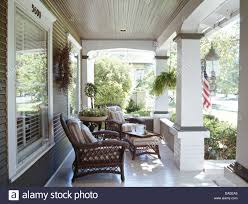 Colonial Style House by Wicker Armchairs On Veranda Of American Colonial Style House Stock