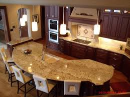 an l shaped kitchen with an oddly shaped island that doubles as an