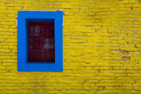 blue trim around window in yellow painted stone wall free stock