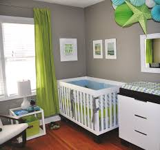 green and white bedding set on white stained wooden baby crib