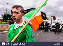 an irish republican man holding a tricolour flag and wearing an