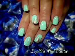mint green nails with small gems and golden feather design hand