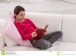 teen sitting on couch at home and reading a stock photo