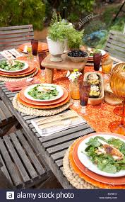 table setting for spring garden party with spinach on orange