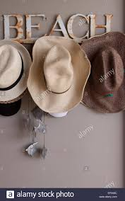 rusty beach named hat rack with straw beach hats and silver fish