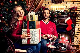 happy young people give each other gifts by the fireplace near