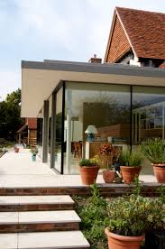 flat roofed and glass walled extension to traditionally built