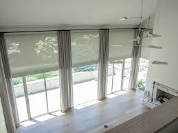 motorized sheer white solar shades and tall tan drapery cover huge