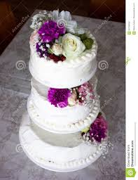 closeup of white wedding cake with brown ribbon and flowers on top